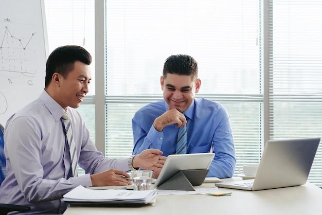 Zwei fröhliche manager, die beim brainstorming ideen generieren
