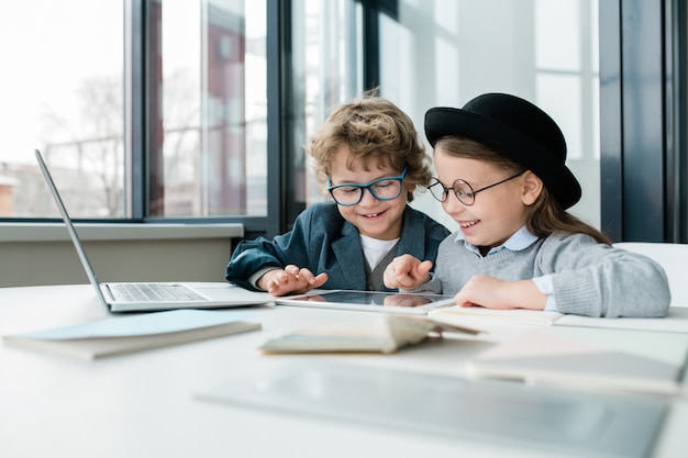 Zwei fröhliche schulfreunde mit digitalem tablet, die durch online-informationen schauen, während sie am schreibtisch sitzen