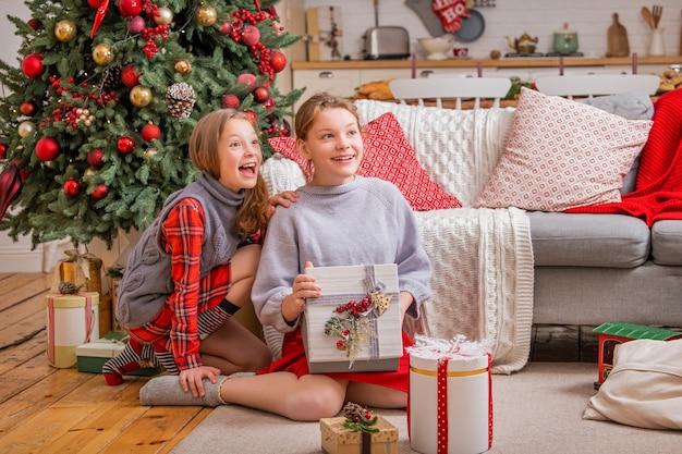 Zwei fröhliche schwestern sitzen zu hause in der nähe des weihnachtsbaums und betrachten kisten mit geschenken