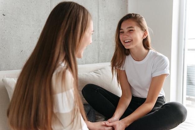 Zwei fröhliche teenager-freundinnen, die sprechen, während sie zu hause auf einer couch sitzen