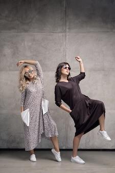 Zwei fröhliche trendige junge frauen, die sonnenbrillen tragen