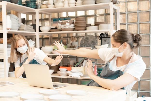 Zwei fröhliche weibliche handwerker mit gesichtsmaske, die im töpferstudio stehend steht