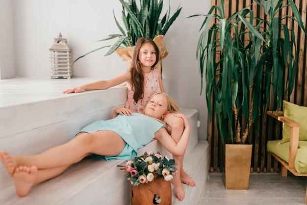 Zwei fröhliche weibliche kinder mit freudigem gesichtsausdruck umarmen