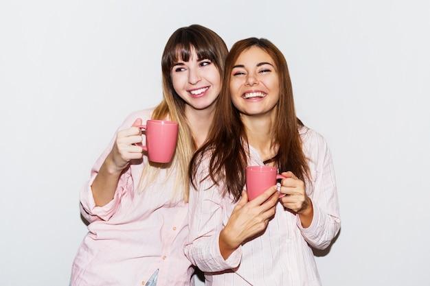 Zwei fröhliche weiße frauen im rosa pyjama mit der tasse tee, die aufwirft. flash-porträt.