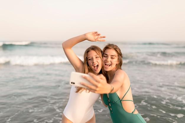 Zwei frohe freundinnen, die selfie vor meereswellen nehmen