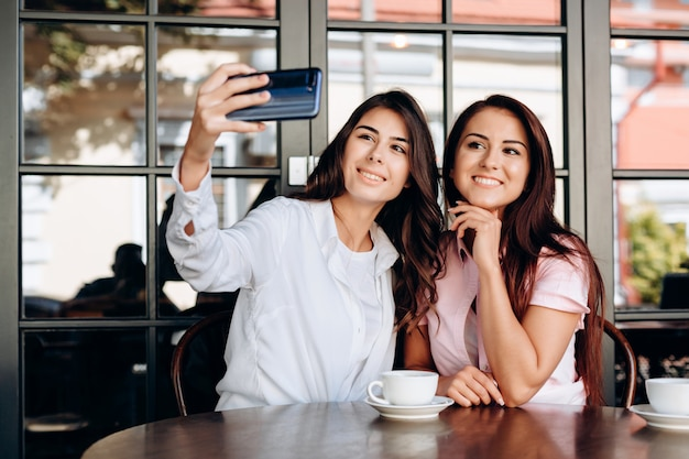Zwei frohe nette mädchen, die ein selfie beim am café zusammen sitzen nehmen