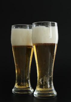 Zwei frostige gläser kaltes goldenes bier mit blasen auf schwarzem hintergrund. alkohol trinken auf party, feiertagen, oktoberfest oder st. patrick's day.