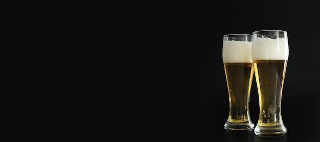 Zwei frostige gläser kaltes goldenes bier mit blasen auf schwarzem hintergrund. freier speicherplatz für text, kopienraum, banner. alkohol trinken auf party, feiertagen, oktoberfest oder st. patrick's day.