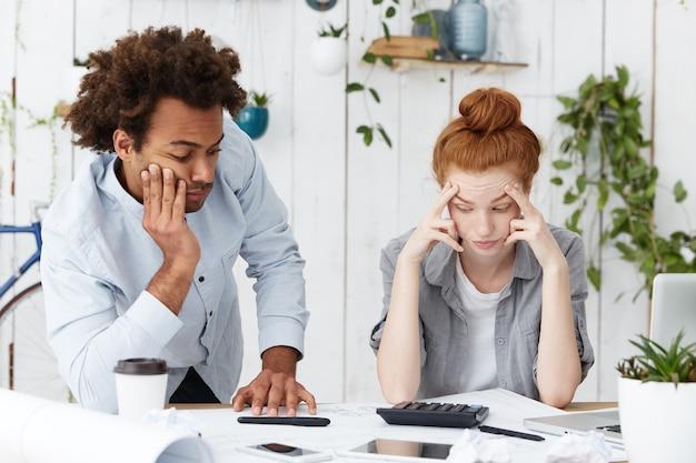 Zwei frustrierte müde ingenieure oder architekten, die gemeinsam an einem architekturprojekt arbeiten