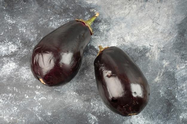 Zwei ganze auberginengemüse auf einen marmortisch gelegt.