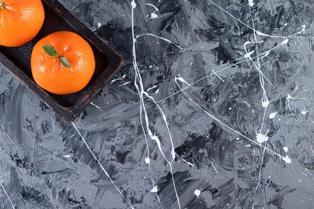 Zwei ganze frische orangenfrüchte auf einem holzbrett.
