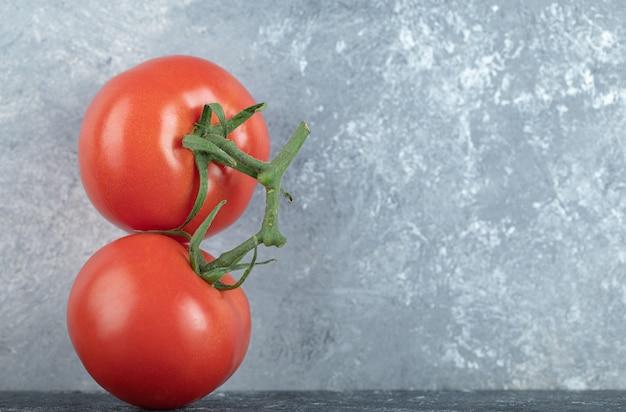 Zwei ganze frische saftige tomaten auf grau.