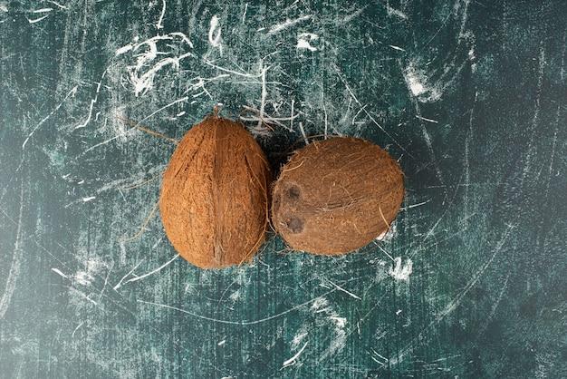 Zwei ganze kokosnüsse auf marmoroberfläche.