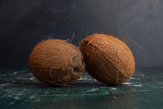 Zwei ganze kokosnüsse auf marmortisch.