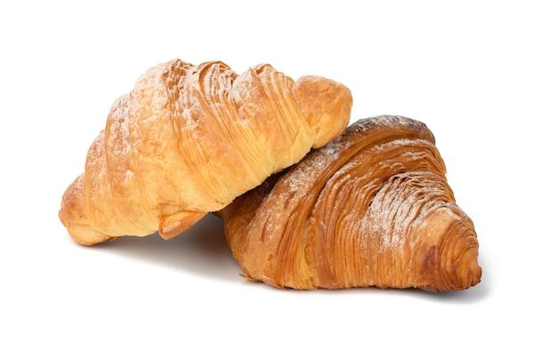 Zwei gebackene croissants auf weißem, isoliertem hintergrund, dessert zum frühstück mit puderzucker bestreut