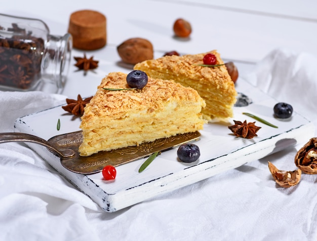 Zwei gebackene kuchen napoleon mit sahne auf einem weißen hölzernen brett