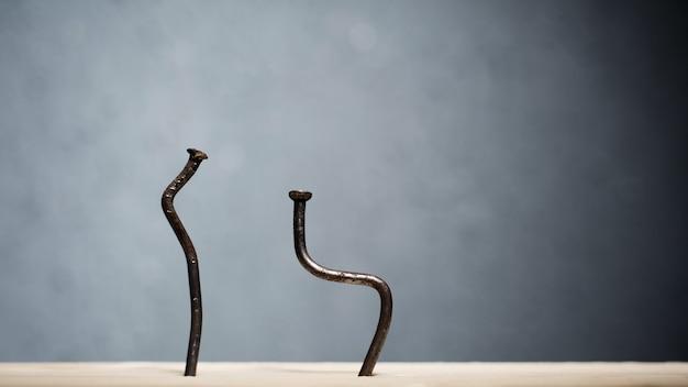 Zwei gebogene nägel in ein brett getrieben. konzept bücken, ischias und degenerative bandscheibenerkrankung - bild