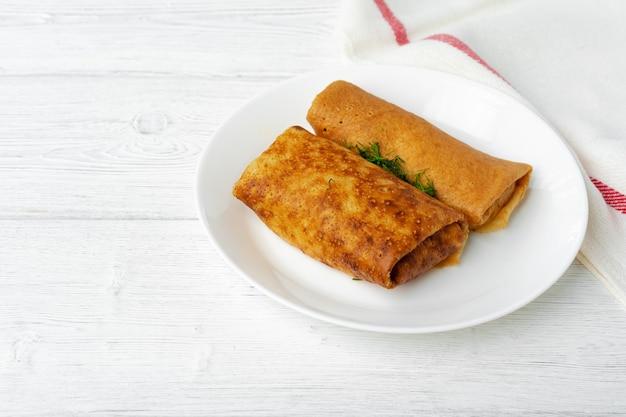 Zwei gebratene russische pfannkuchen im teller auf weißem holztisch