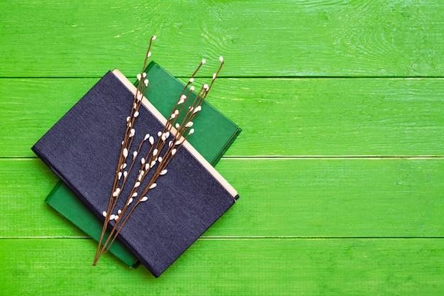 Zwei gebundene bücher auf einem grünen holz und weidenzweigen. ansicht von oben
