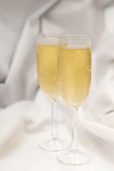 Zwei gefüllte champagnerglas über weißem textil