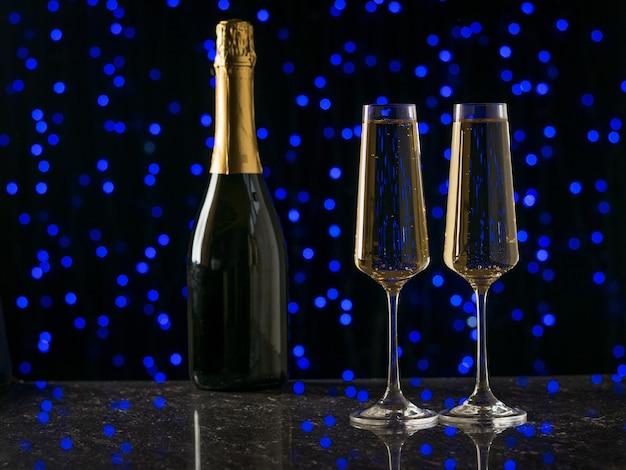 Zwei gefüllte gläser und eine flasche sekt auf blauen bokeh-lichtern. ein beliebtes alkoholisches getränk.