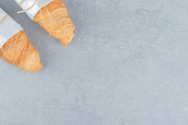 Zwei geknotete croissants auf dem marmorhintergrund. hochwertiges foto