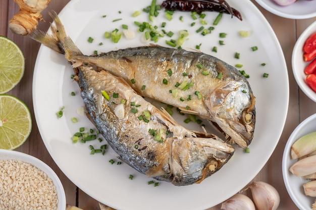 Zwei gekochte makrelen, in eine weiße schüssel gelegt und mit frühlingszwiebeln bestreut.