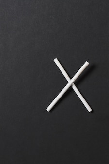 Zwei gekreuzte weiße zigaretten wie buchstabe x auf schwarzem hintergrund