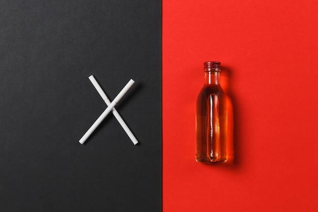 Zwei gekreuzte weiße zigaretten wie buchstabe x, flasche mit alkohol cognac, whisky