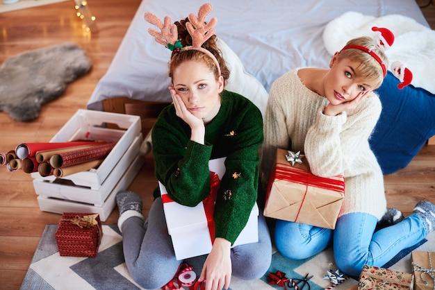 Zwei gelangweilte mädchen, die weihnachtsgeschenke für weihnachten vorbereiten