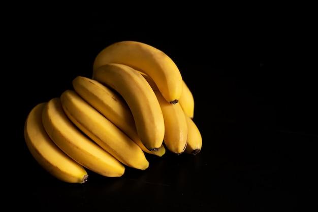 Zwei gelbe bananen auf dem schwarzen hintergrund
