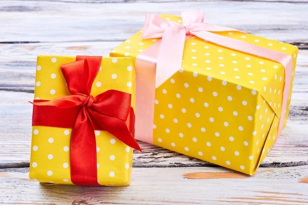 Zwei gelbe geschenkboxen, hölzerner hintergrund.