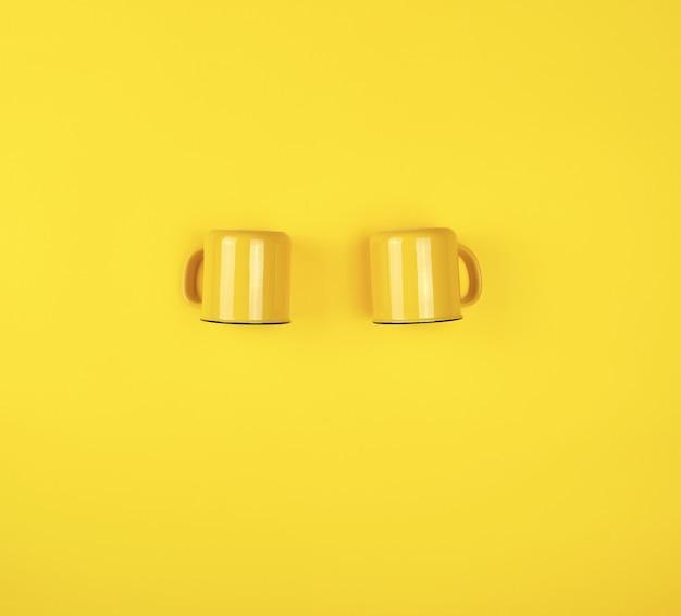Zwei gelbe keramikschalen mit einem griff auf gelb