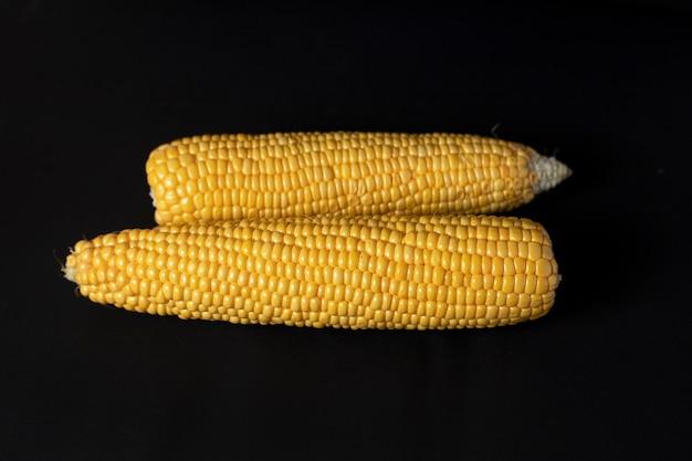 Zwei gelbe mais liegen auf einem schwarzen feld