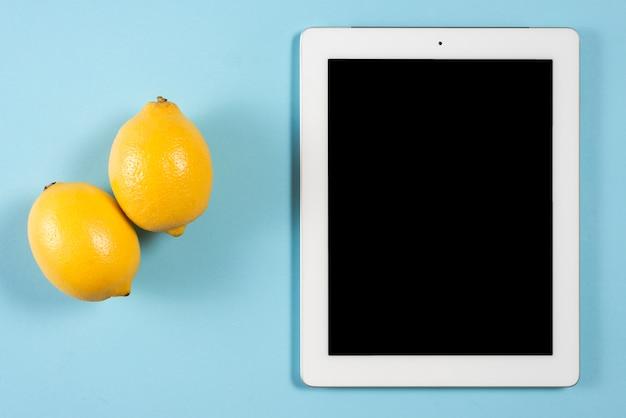 Zwei gelbe saftige zitronen nahe der digitalen tablette mit schwarzem bildschirm gegen blauen hintergrund