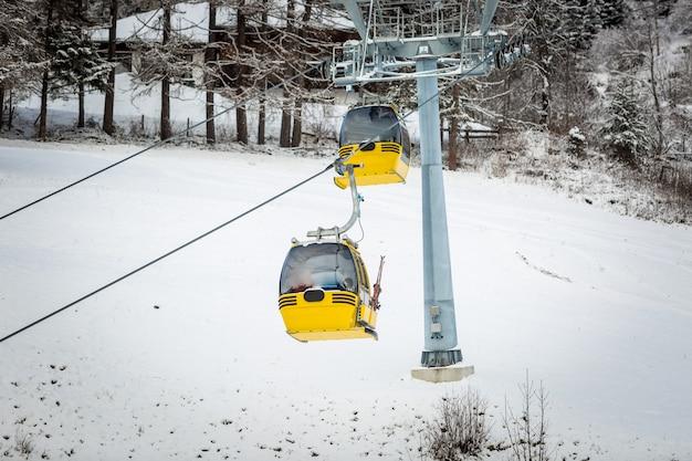 Zwei gelbe seilbahnen auf der skipiste in den österreichischen alpen