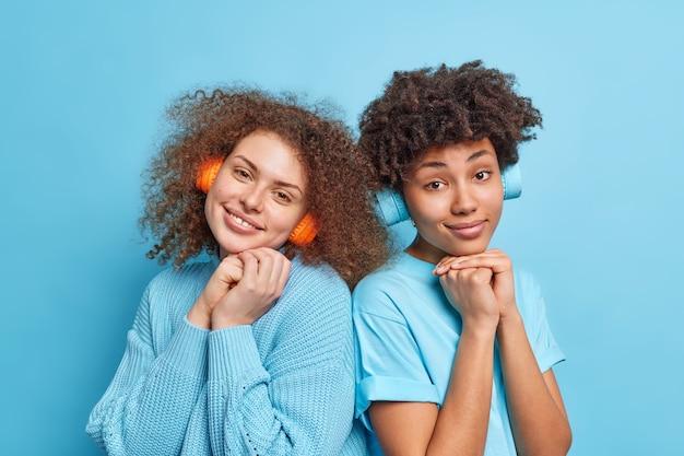 Zwei gemischte beste freunde, die beiläufig gekleidet sind, stehen eng beieinander und hören audiospuren in drahtlosen kopfhörern, verbringen freizeit zusammen isoliert über blauer wand. menschen-hobby-konzept