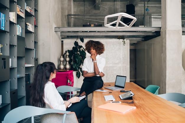 Zwei gemischtrassige junge geschäftsfrauen, die sitzung im modernen büro haben