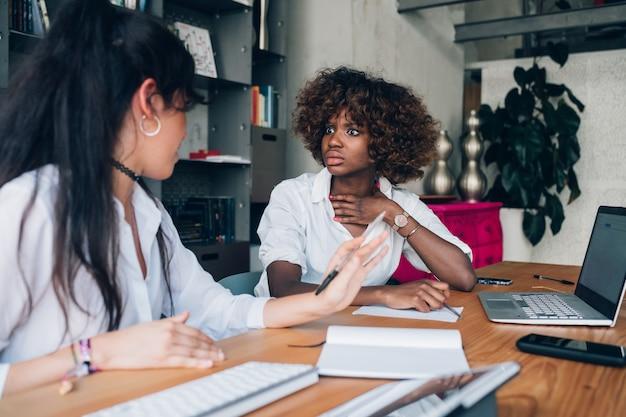 Zwei gemischtrassige studenten diskutieren ein projekt in einem büro, in dem sie zusammenarbeiten