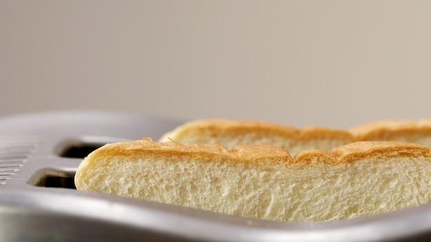 Zwei geröstetes toastbrot, das aus der toastermaschine springt, während rauch austritt.