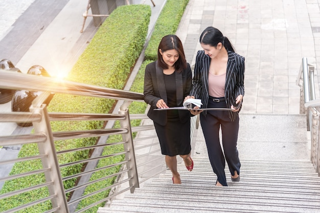 Zwei geschäftsfrauen, die auf treppe aufwachen und zusammen sprechen