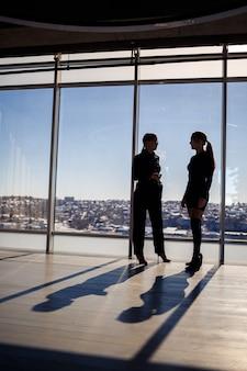 Zwei geschäftsfrauen, die den blick auf die stadt genießen und sich unterhalten, während sie am großen fenster im büro stehen