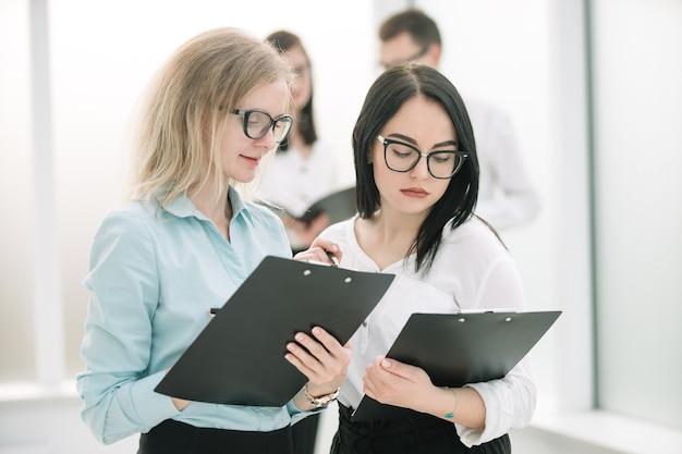 Zwei geschäftsfrauen, die geschäftsdokumente besprechen, die im büro stehen