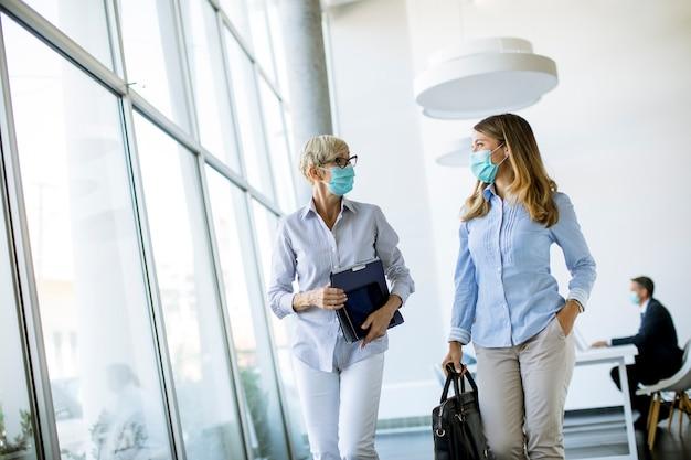 Zwei geschäftsfrauen, die im büro gehen und maske als virenschutz tragen