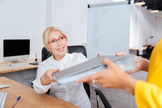 Zwei geschäftsfrauen, die im büro mit ordnern arbeiten