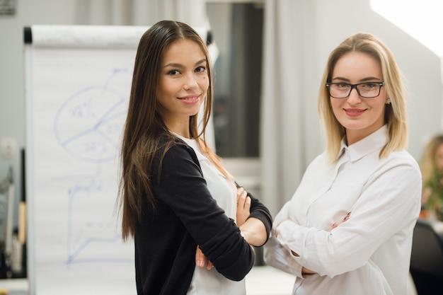 Zwei geschäftsfrauen, die in einem büro stehen und lächeln