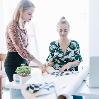 Zwei geschäftsfrauen, die karierte flagge auf diagramm im büro vorbereiten