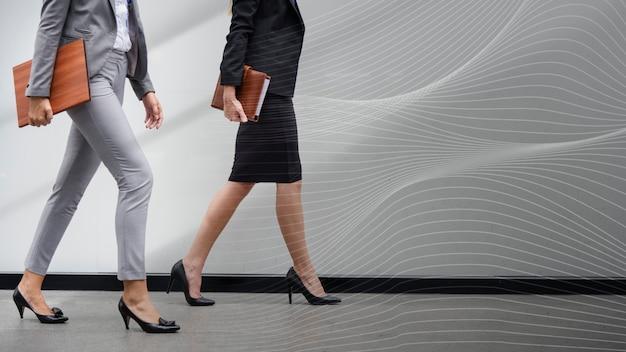 Zwei geschäftsfrauen gehen in einem korridor