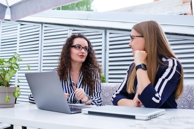 Zwei geschäftsfrauen sitzen mit laptop und geschäftspapieren in einem hellen café und unterhalten sich mit ernsthaften leuten. büroangestellte sitzen in kaffeepausen und arbeiten. geschäftstreffen in einem café