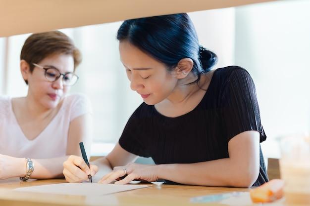 Zwei geschäftsfrauen unterzeichnen vertragsvereinbarung während des treffens im café.